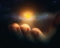 Miniature universe. A miniature universe rests on the finger tips of a hand Stock Image