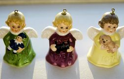 Miniature, Vintage, and Colourful Angel Bells are Rear Life by Heavenly Sunshine on a Shelve during Christmas Season. Each precious angelic winged ornament is Stock Photos