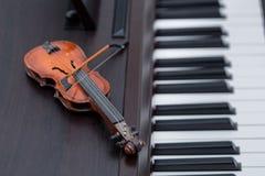 Miniature violine on dark wooden piano. A miniature violine on dark wooden piano royalty free stock photos