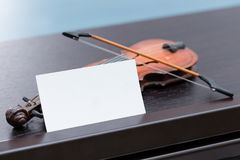 Miniature violine on dark wooden piano with blank business card. A miniature violine on dark wooden piano with blank business card royalty free stock image