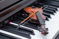 Miniature violine on dark wooden piano. A miniature violine on dark wooden piano royalty free stock image
