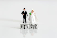 Miniature wedding couple with the word love on beads Royalty Free Stock Image