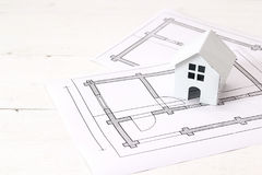 Miniature white toy house with house plan drawing on white woode Royalty Free Stock Photography