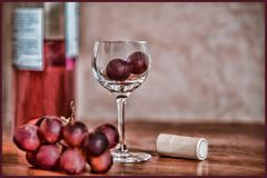Tiny wine glass filled with red grapes. Miniature wine glass with red grapes, grunge texture, blank cork for customization royalty free stock photo