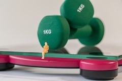 Miniature woman figure siting on the digital electronic bathroom scale for weight of human body. Green dumbbells at shallow depth royalty free stock images
