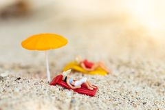 Miniature woman wearing swimsuit relaxing on the beach at the sea. Image use for travel business concept Royalty Free Stock Images