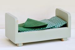 Miniature wooden bed for doll. Gray, miniature wooden bed for doll. Doll bedding. Toy for child Royalty Free Stock Photos