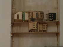 Miniature wooden buildings on display on a wooden shelf against a wall stock photos