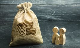 Miniature wooden family figurines stand near a money bag. The concept of savings. Budget planning. Distribution of profits. stock photography