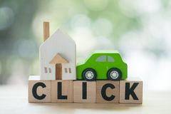 Miniature wooden home and wooden car on wood block with words CLICK. Miniature wooden home and wooden car on wood block with words `CLICK`. Concept of rent a car royalty free stock photo