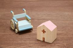 Free Miniature Wooden Hospital And Blue Wheelchair On Wood. Stock Photo - 110587310