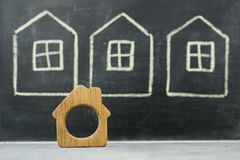 Miniature wooden house on drawn houses background Stock Photos