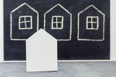 Miniature wooden house on drawn houses background Stock Photo