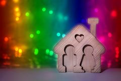 Miniature wooden house with heart, man and woman inside on bright multicolored background with lights. Love and happy family royalty free stock image