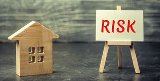 Miniature wooden house and the inscription ` Risk ` . Buying a house, apartment and financial risks. Loss of property for failure stock photos