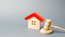 Miniature wooden house and judge`s hammer. The concept of resolving property disputes. Property alienation. Confiscated housing. royalty free stock photo