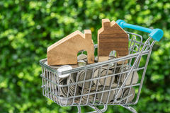 Miniature wooden house in mini shopping cart with full of coins Stock Images