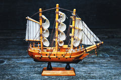Miniature wooden model of sailboat on a wooden background Royalty Free Stock Images