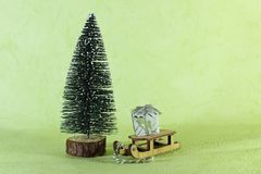 Miniature wooden sledge carrying a small gift next to a bright green Christmas tree on a light green background Stock Photos