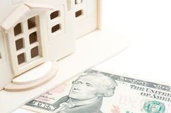 Miniature wooden toy house on 10 dollar bill. white background Stock Photography