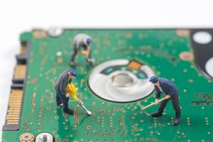 Miniature worker are digging a hole on hard disk electronic boar. D royalty free stock images