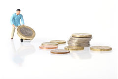 Miniature worker drives euro coins Stock Image