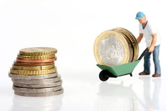 Miniature worker drives euro coins Royalty Free Stock Photography