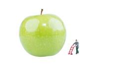 Miniature worker on fresh green apple Royalty Free Stock Photos