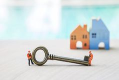 Miniature worker with safety jacket moving vintage metal key Stock Photo