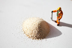 Miniature worker and a stack of sand Royalty Free Stock Photo