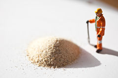 Miniature worker and a stack of sand Royalty Free Stock Image