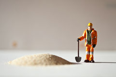 Miniature worker and a stack of sand Stock Photos