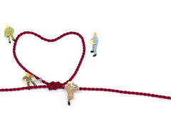 Miniature worker team building Heart Shaped with rope. On white background Stock Photo
