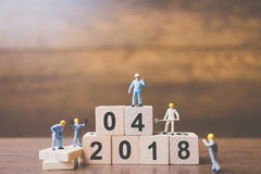 Miniature worker team building number on wooden block. Happy new year  2018 Stock Photography