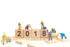 Miniature worker team building number on wooden block. Happy new year  2018 Royalty Free Stock Photos