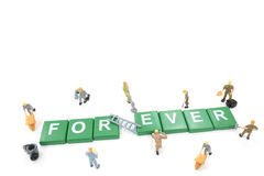 Miniature worker team building word forever Stock Photography