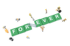 Miniature worker team building word forever Royalty Free Stock Image
