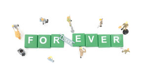 Miniature worker team building word forever Stock Image