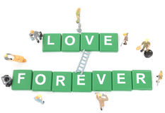 Miniature worker team building word love forever Stock Photos