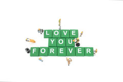 Miniature worker team building word love you forever. On white background stock photos