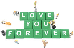 Miniature worker team building word love you forever. On white background stock images