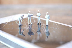 Miniature worker team  restore broken screen on a smartphone. Selective and soft focus Stock Images