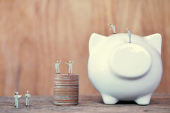 Miniature worker team and white piggy bank on wood concept to sa Stock Images