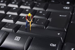 Miniature Worker On Top Of Black Computer Keyboard Stock Images