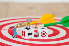 Miniature worker toy with dice on red dart board Stock Photography