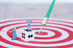 Miniature worker toy with dice on red dart board Stock Image