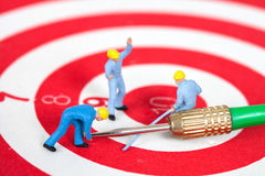 Miniature worker toy on red dart board with green dart Stock Images