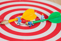 Miniature worker toy on red dart board with green dart Stock Photo