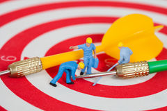Miniature worker toy on red dart board with green dart Stock Photography