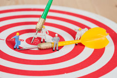 Miniature worker toy on red dart board with yellow  arrow Stock Photo